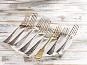 Acht Gabeln nebeneinander auf Teller liegend