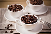 Three White Coffee Cups on White Saucers Filled with Coffee Beans