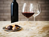 Two Wine Glass; One with Red Wine and One Empty; Chocolate Dipped Cookies on a Plate