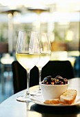 Sautéed olives with chorizo and white bread served with glasses of white wine