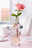 Flasche als Vase mit Rose und Herzanhänger