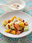 Exotic fruit salad with pomegranate seeds and yoghurt