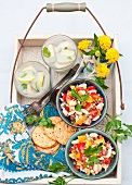 Two Bowls of Cherry Tomato and Bean Salad with Feta Cheese; Crackers and Drinks on a Tray