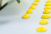 Mixture for yellow macaroons being piped onto grease-proof paper