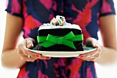 Woman Holding a Plate with a Cake Decorated with a Green Ribbon and Bow and Topped with Crushed Candy