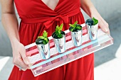 A Woman Carrying a Tray of Mint Drinks in Small Cups