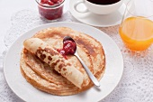 Pancakes with jam, coffee and orange juice