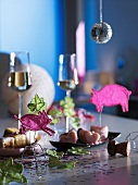Hand-crafted animal figures and petits fours on dishes, with glasses of sparkling wine in the background