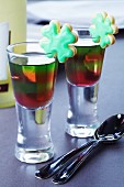 Layered jelly in glasses decorated with clover leaf-shaped biscuits