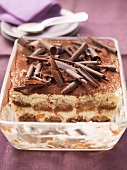 Tiramisu topped with chocolate curls, in a glass dish, part already served