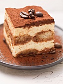 A piece of tiramisu with mocha beans and cocoa powder
