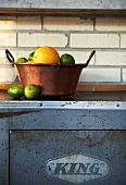 Oranges and Limes in a Copper Pot on a Counter