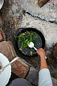 Removing Sauteed Rapini Out of an Iron Skillet Over a Fire Pit
