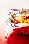 Smoked Chili Dog Topped with Cheesy Macaroni and Cheese; In a Plastic Basket