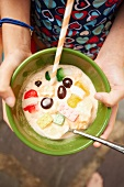 Person Holding a Bowl of Melting Ice Cream with Candies, a Straw and a Spoon