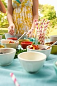 Table Set Up Outside with Bowls of Ice Cream and Toppings; Straws