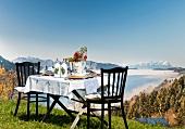 Gedeckter Tisch im Landhaus-Stil auf einer Almwiese mit Alpenpanorama