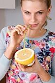 Frau trinkt mit Strohhalm aus einer Grapefruit
