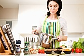 A woman with a saucepan and ingredients in the kitchen
