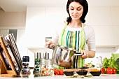 Frau mit Kochtopf und Zutaten in der Küche