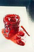 Strawberry jam in a jar; some spilt