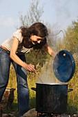 A woman stirring a large pot over an open fire