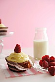 A raspberry cupcake with fresh raspberries and a bottle of milk
