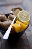 Fresh ginger root, orange wedges and half a lemon