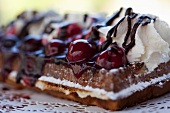 Fresh waffles with cherries, cream and chocolate