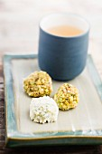 Chocolate truffles with pistachios and white chocolate, with a mug of tea