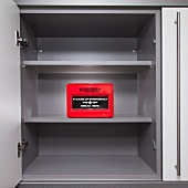 A metal container with emergency food store in an empty kitchen cupboard