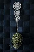 Sencha tea leaves on an Oriental silver spoon