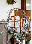 Wintery wreath of twigs and leaves on chair on veranda