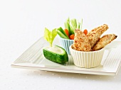 Chicken fingers (breaded chicken fillets) and crudités with a yoghurt dip