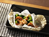 Prawns with broccoli florets wrapped in grease-proof paper
