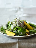 Spinach salad with edible shoots and fruit