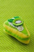 A fabric toy shaped like a slice of kiwi tart