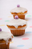 Three cupcakes topped with icing and marzipan eggs for Easter