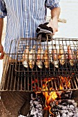 A man barbecuing fish