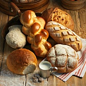 Assorted types of bread and a Hefezopf (sweet bread from southern Germany) on a rustic wooden surface