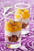 A layered dessert with oranges, gingerbread, whipped cream and poppy seeds