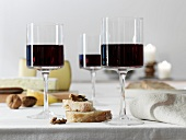 Glasses of red wine in front of a cheeseboard with bread