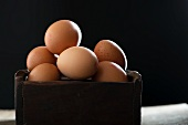 Fresh brown eggs in a wooden box