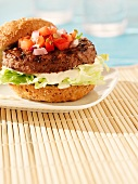 A beefburger in a bun with mayonnaise, salad and salsa