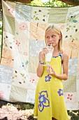 Blondes Mädchen trinkt Milchshake im Freien
