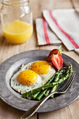 Two Fried Eggs with Sauteed Asparagus and Strawberries; Orange Juice in a Mason Jar
