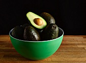 Avocados in a Green Bowl; One Halved