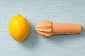 A lemon and a lemon squeezer on a wooden surface