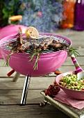Lamm-Rosmarin-Spiesse auf einem rosa Grill und Taboule