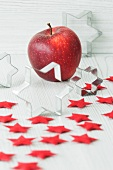 Weihachtsdekoration mit Ausstechförmchen, roten Filzsternen und Apfel